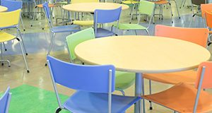 Class room with round tables and pastel colored chairs